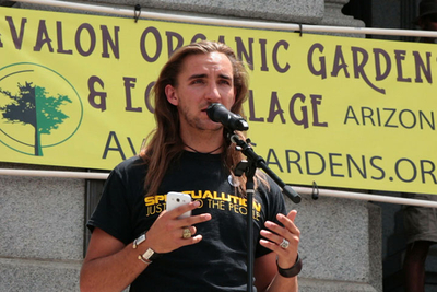 Amadon DellErba speaks on stage at the March Against Monsanto Denver, Colorado protest, sharing a message for food-independence by working cooperatively, creating communities, and growing organic food